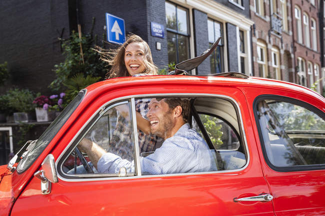 Happy couple with small car in the city — Stock Photo