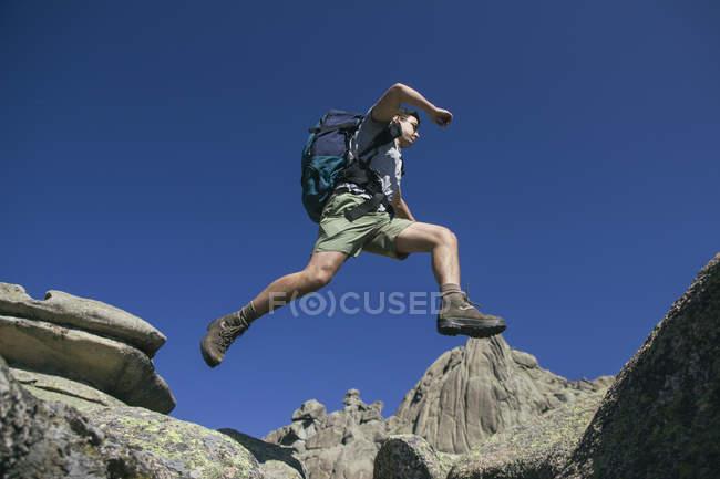Espagne, randonneur avec sac à dos sautant sur les rochers à La Pedriza — Photo de stock
