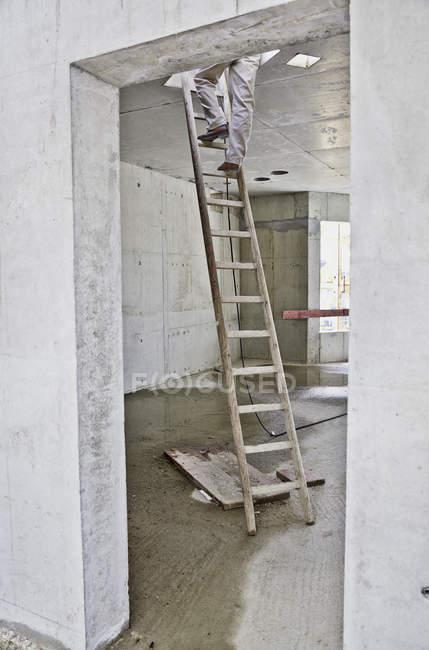 Uomo sulla scala in cantiere — Foto stock