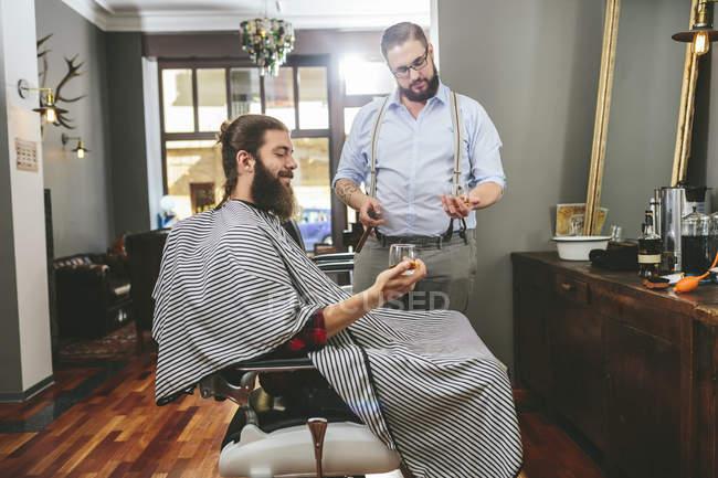 Перукарня та клієнт пити дух від тумблери в перукарні — стокове фото