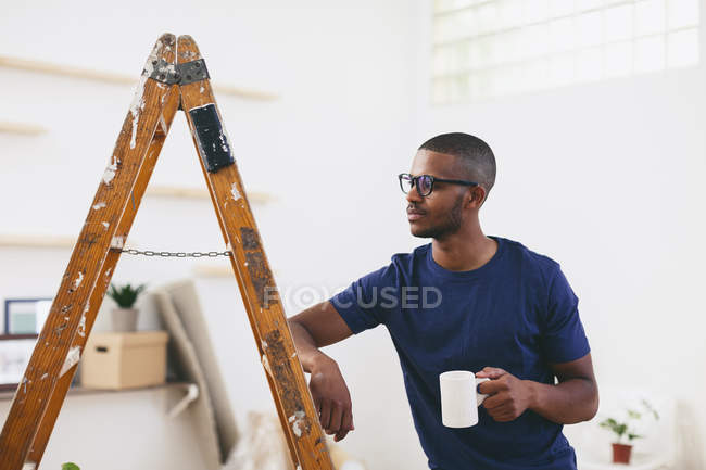 Young man leaning on step ladder having a coffee break — Stock Photo