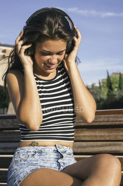 Smiling teenage girl hearing music with headphones — Stock Photo