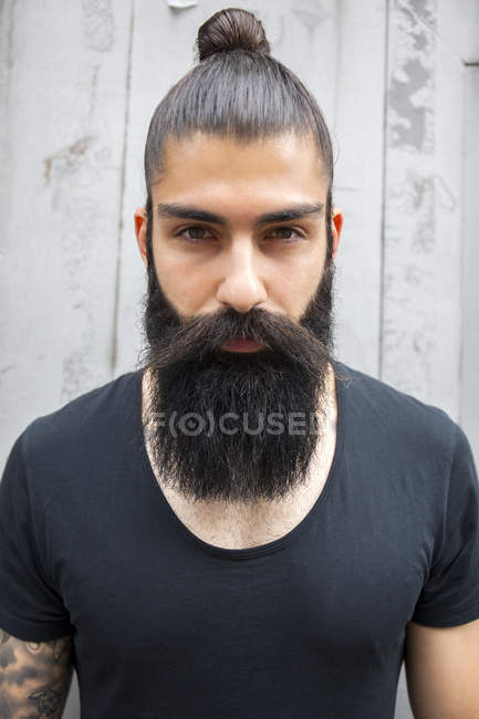 Portrait of young man with full beard and bun — Stock Photo