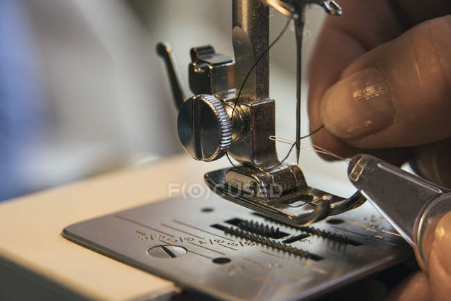 Woman adjusting thread in a sewing machine — Stock Photo