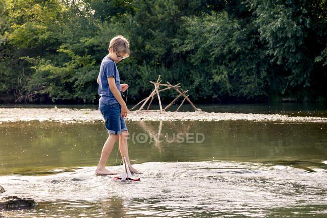 Хлопчик грає з дерев'яна іграшка човен в річці — стокове фото