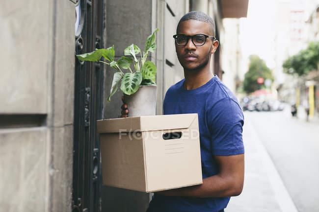 Spanien, Barcelona, Porträt des jungen Mannes mit Karton und Blattpflanze vor einem Haus — Stockfoto