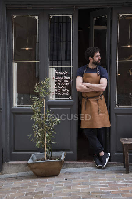 Craftsman with leather apron and arms crossed standing at the entrance of his workshop — Stock Photo