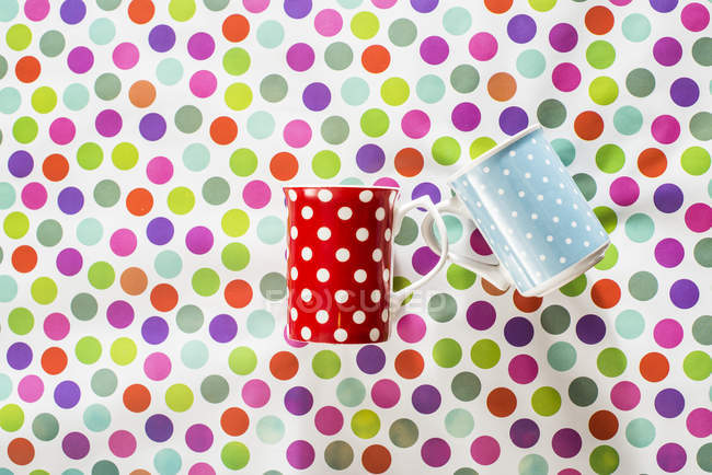 Cups with white points on colorful background — Stock Photo