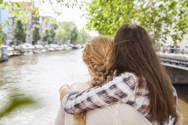 Netherlands, Amsterdam, two women embracing at town canal — Stock Photo