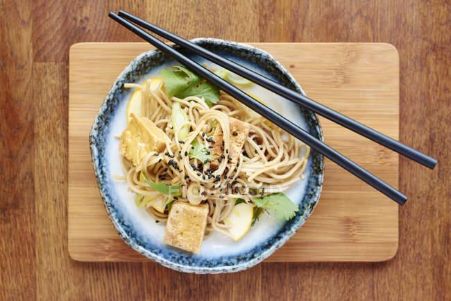Asiatischer Nudelsalat mit Soba-Nudeln, Tofu, Frühlingszwiebeln, gelbe Zucchini und Koriander, garniert mit schwarzem Sesam — Stockfoto