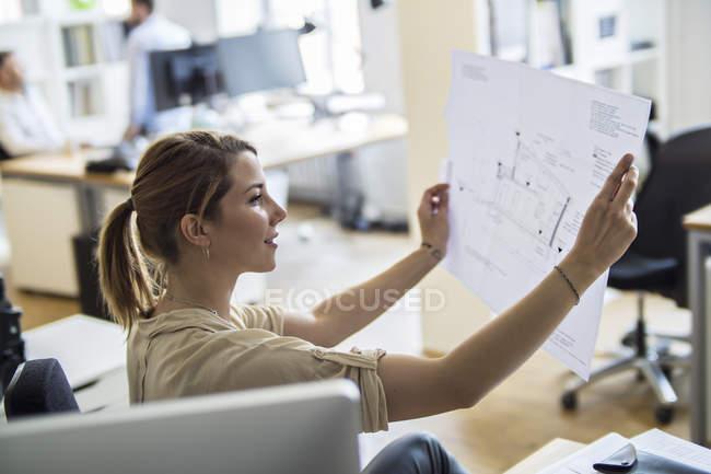 Frau im Amt schaut sich Plan an — Stockfoto