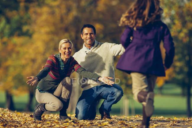 Filha correndo para seus pais em um parque em um dia ensolarado de outono — Fotografia de Stock