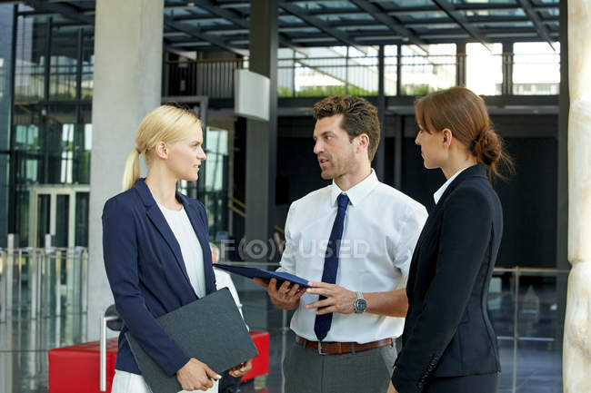 Three business colleagues discussing in office lobby — Stock Photo