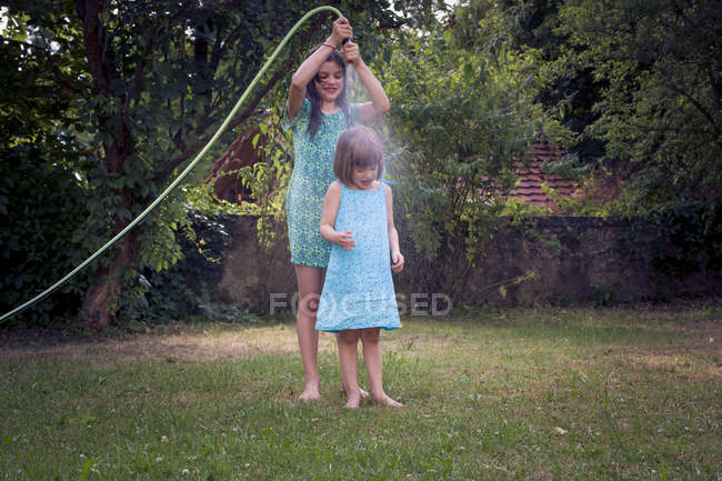 Two sisters using garden hose on lawn — Stock Photo