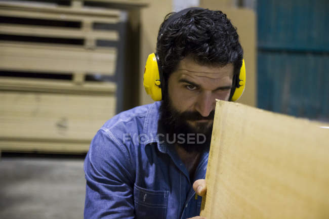Craftsman with hearing protection examining a wooden plank — Stock Photo