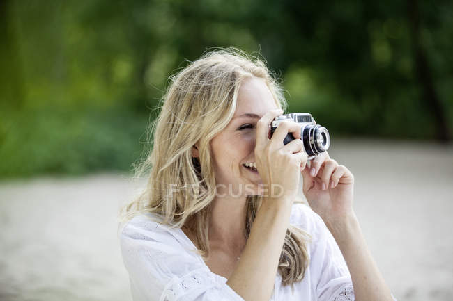 Smiling blond woman taking a photo with an old camera — Stock Photo