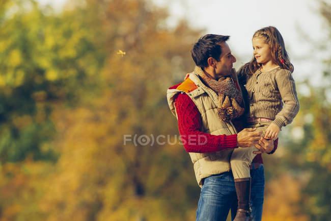 Vater trägt seine kleine Tochter an einem Herbsttag in einem Park — Stockfoto