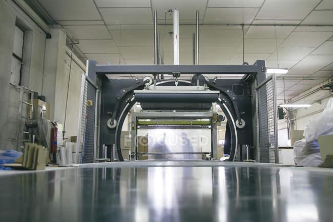 Силуэты сотрудников за упаковочной машиной на заводе — стоковое фото