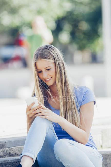 Портрет улыбающейся девочки-подростка, сидящей на ступеньках и читающей текстовое сообщение на мобильном телефоне — стоковое фото