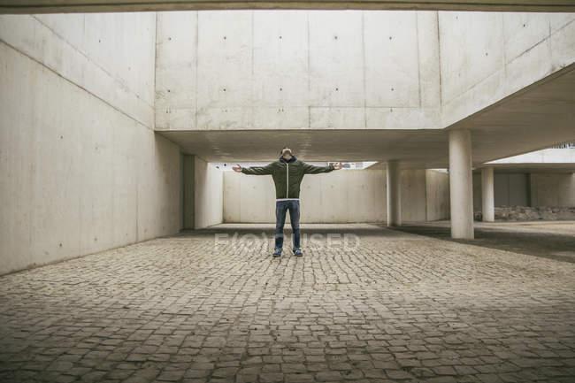 Hombre con los brazos extendidos y cabeza hacia atrás en la arquitectura moderna - foto de stock