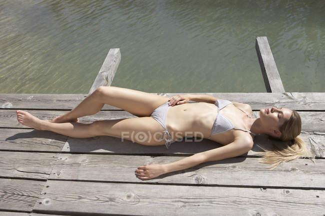 Жінку загоряти на сонці палубі — стокове фото