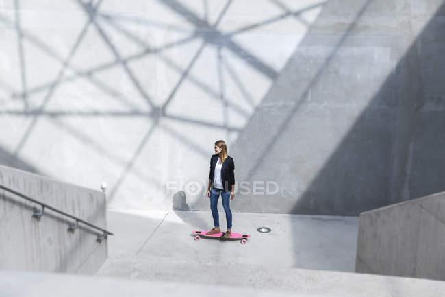Бізнес-леді з рожевими скейтборд в сучасній архітектурі — стокове фото