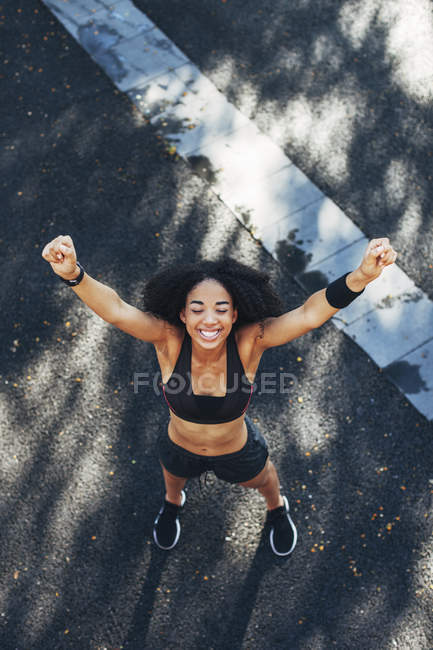 Jogger with arms up standing on road — Stock Photo