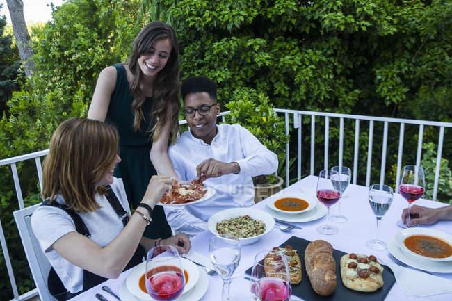 Женщина предлагает гостям испанскую ветчину во время летнего ужина — стоковое фото