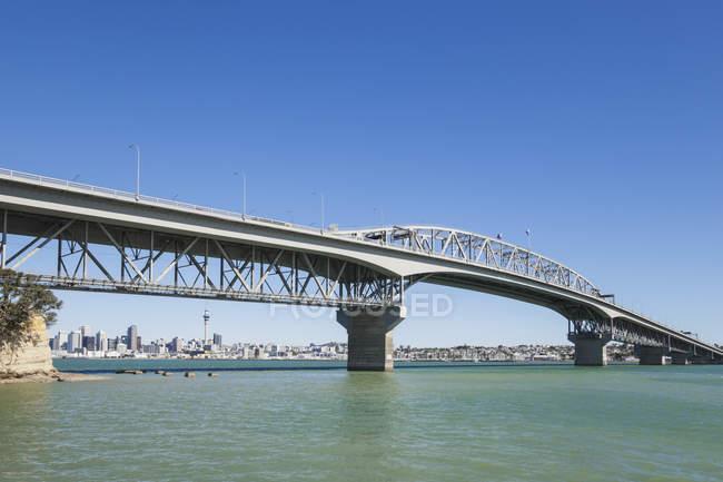 Nuova Zelanda, Auckland, Harbour Bridge con Skyline contro l'acqua — Foto stock