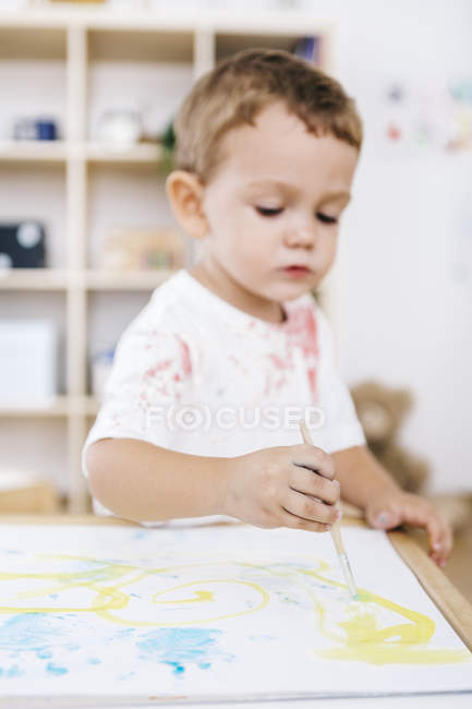 Concentrated Little boy painting with watercolours — Stock Photo