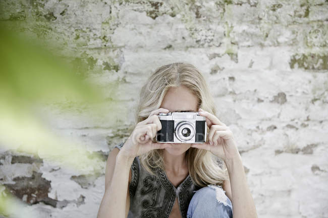 Blond woman taking a photo with an old camera — Stock Photo