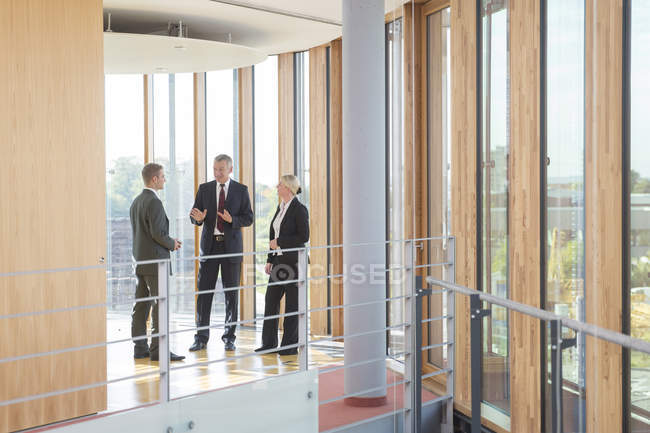 Three business people communicating in office building — Stock Photo