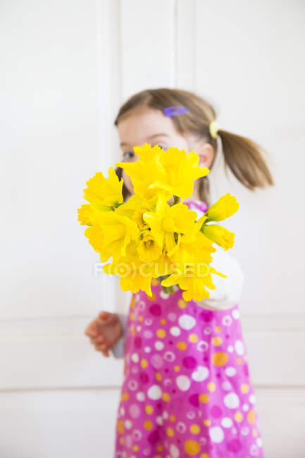 Little girl showing bunch of daffodils — Stock Photo