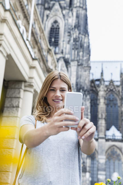 Germany, Cologne, portrait of young woman taking a selfie with smartphone — Stock Photo