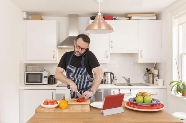 Homem telefonando com smartphone enquanto prepara os legumes na cozinha — Fotografia de Stock
