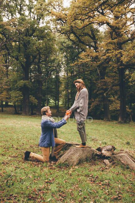 Mann kniete und schlägt vor, Freundin — Stockfoto