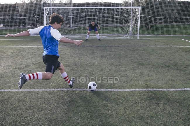 Fußballer kickt mit einem Torwart einen Ball vor ein Tor — Stockfoto