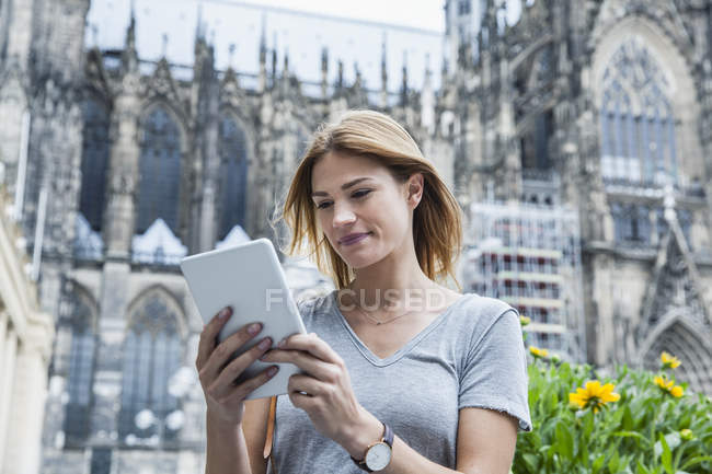 Germany, Cologne, portrait of young woman with mini tablet in front of Cologne Cathedral — Stock Photo