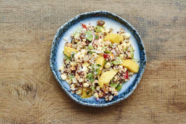 Insalata di quinoa con mango, carote, fagioli di fava, peperone rosso, cipolla rossa, mais, cocco e uvetta targhetta applicata sul legno superficie vista superiore — Foto stock