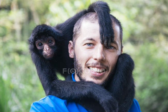 Bolivia, Coroico, portrait of smiling man with black spider monkey on shoulders — Stock Photo