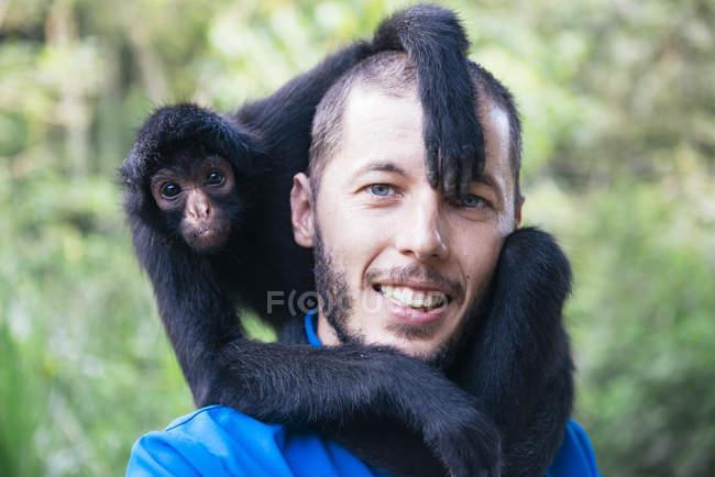 Bolivie, Coroico, portrait d'un homme souriant avec un singe araignée noir sur les épaules — Photo de stock
