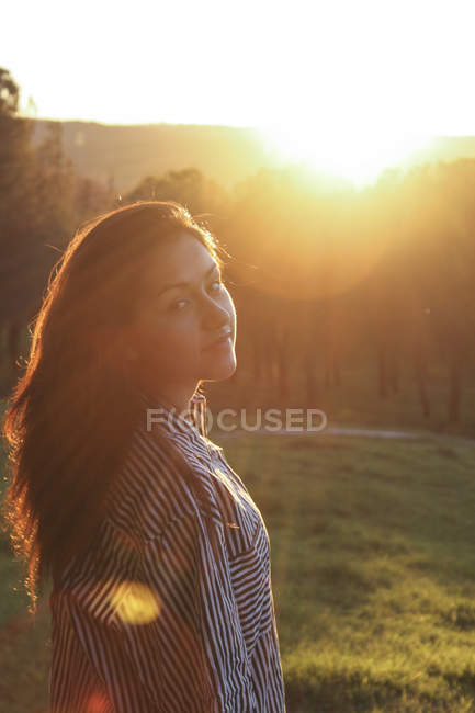 Portrait of woman in a park at backlight — Stock Photo