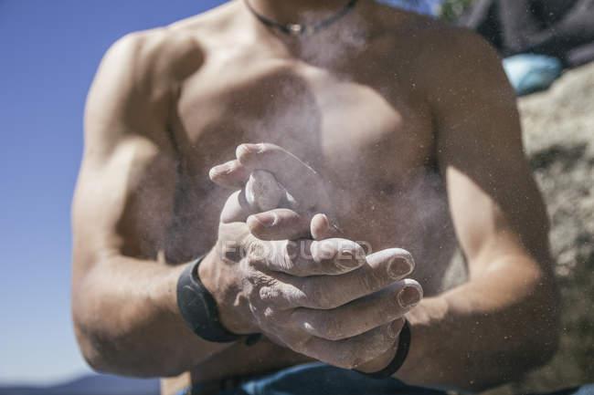 Hemdloser Bergsteiger, der seine Hände mit Magnesiumpuder umhüllt — Stockfoto