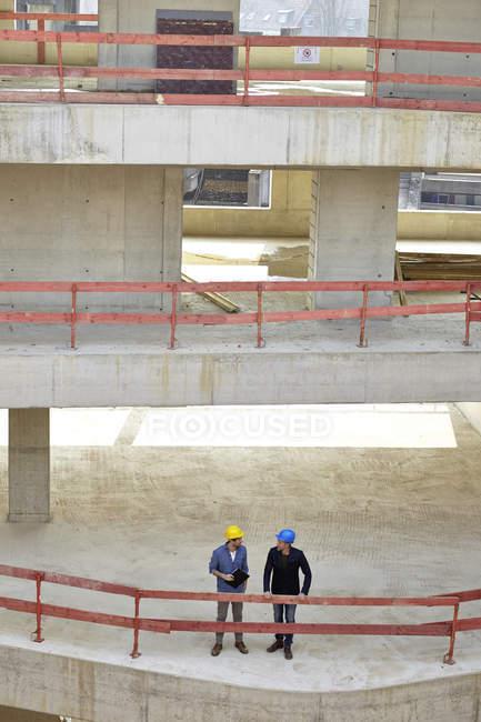 Due uomini con i cappelli duri che parlano in cantiere — Foto stock