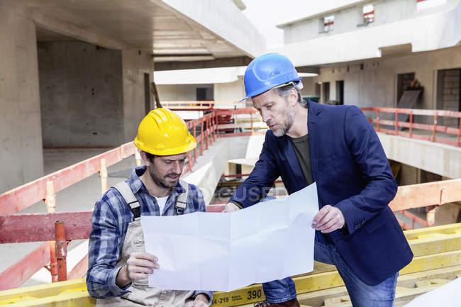 Строителем и архитектором с планом говорить на строительной площадке — стоковое фото