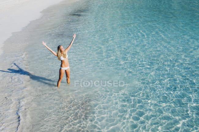 Испания, Майорка, женщина, стоящая в море с вытянутыми руками — стоковое фото