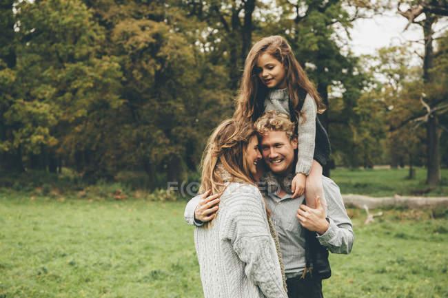 Jeune couple avec petite fille sur les épaules de son père au parc automnal — Photo de stock