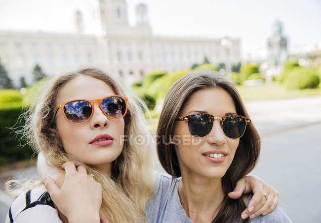 Austria, Vienna, two young women embracing with Museum of Art History in background — Stock Photo