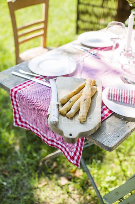 Puesto mesa en jardín con productos horneados - foto de stock