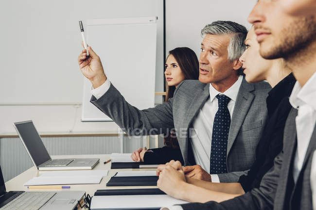 Business people sitting in office listening to presentation — Stock Photo
